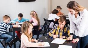画在类的老师和基本的年龄孩子 库存照片