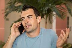 在他的耸肩他肩膀问的手机的男性模型 免版税库存照片