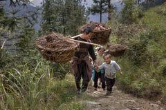 在他的肩膀的农夫运载的竹篮子 免版税库存图片