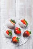 在轻的背景关闭的黑暗和白色巧克力蘸的新鲜的草莓  可口点心和棒棒糖 库存图片