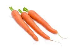 在轻的背景的三棵红萝卜 免版税库存照片