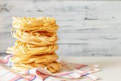 在轻的背景的意大利意大利细面条巢面团 免版税库存图片