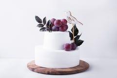 在轻的背景的白色两层蛋糕 免版税库存图片