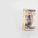 在轻的背景的美元卷 免版税库存照片