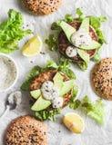 在轻的背景的金枪鱼汉堡,顶视图 与金枪鱼、鲕梨和芥末酱,可口开胃菜的汉堡 免版税库存照片