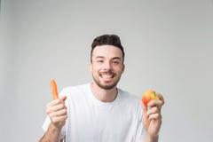 在轻的背景隔绝的一件白色衬衣的一个人拿着红萝卜和苹果 免版税库存图片