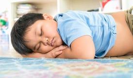 在他的胳膊的肥胖男孩睡眠 免版税图库摄影
