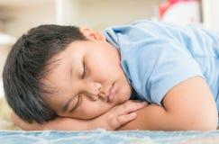 在他的胳膊的肥胖男孩睡眠 库存照片