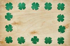 在轻的胶合板背景的纸绿色三叶草三叶草叶子框架 库存图片