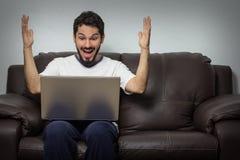在他的膝上型计算机的人读的好消息 免版税库存图片