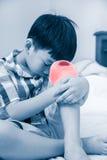 在他的膝盖伤害的孩子 孩子是事故 图库摄影