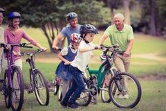 在他们的自行车的愉快的家庭在公园 库存照片