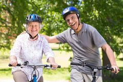 在他们的自行车的愉快的资深夫妇 免版税库存图片