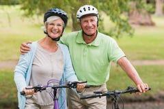 在他们的自行车的愉快的资深夫妇 免版税库存照片