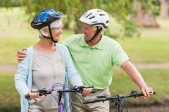 在他们的自行车的愉快的资深夫妇 图库摄影