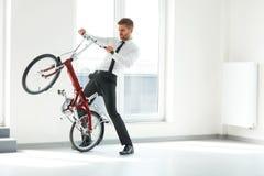 在他的自行车的年轻商人乘驾在办公室 企业例证JPG人向量 免版税库存照片