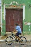 在他的自行车的巴西人骑马在他的房子前面 免版税库存图片