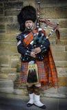 在他的苏格兰男用短裙打扮的苏格兰吹笛者 免版税库存照片