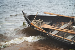 在水的葡萄酒老木小船与波浪 免版税库存照片