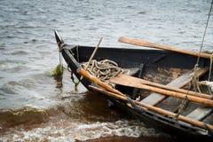 在水的葡萄酒老木小船与波浪 图库摄影