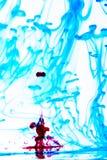 在水的蓝色和红色烟 库存照片