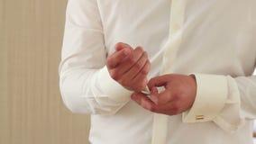 在他的衬衣袖口的新郎按钮 股票录像