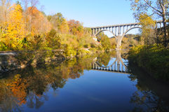 在水的被成拱形的蓝色桥梁 免版税库存图片