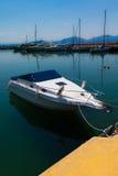 在水的被日光照射了白色和蓝色地中海渔船与风船在背景中在优卑亚岛- Nea Artaki,希腊 免版税库存照片
