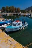 在水的被日光照射了白色和蓝色地中海渔船在优卑亚岛- Nea Artaki,希腊 免版税图库摄影