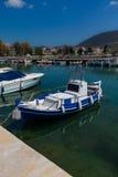 在水的被日光照射了白色和蓝色地中海渔船在优卑亚岛- Nea Artaki,希腊 库存照片