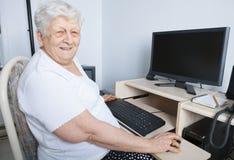 在他的计算机前面的资深人 免版税库存照片