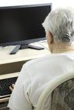 在他的计算机前面的资深人 免版税库存图片