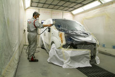 绘在他的车库的工作者一辆汽车 免版税库存照片