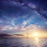 在水的输电线在晚上 神奇满天星斗的天空 积云 免版税库存照片