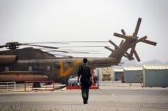 在他的途中的一名飞行员对直升机 免版税库存图片