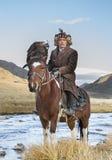 在他的马的蒙古游牧人老鹰猎人 库存照片
