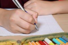 在他的练习本的学生文字在学校 免版税图库摄影