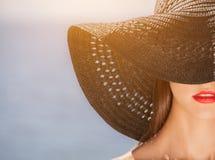 在头戴的黑帽会议的可爱的女孩,在海滩 免版税库存图片