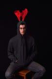 年轻在他的黑有冠乌鸦的人佩带的驯鹿垫铁有滑稽的 库存照片