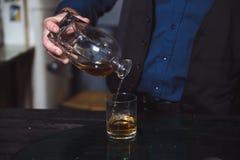 在他的玻璃的商人倾吐的威士忌酒 免版税库存照片