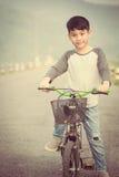 在他的bycicle的亚洲男孩骑马在路 库存图片