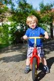 在他的bycicle的小的小孩男孩骑马在夏天 免版税库存图片