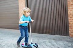 在他的bycicle的小的小孩男孩骑马在夏天 免版税图库摄影