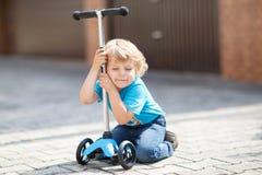 在他的bycicle的小的小孩男孩骑马在夏天 库存图片