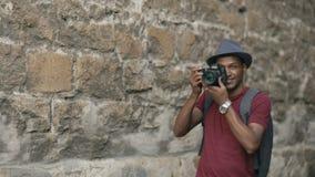 在他的dslr照相机的非裔美国人的愉快的旅游采取的照片 站立在著名大厦附近的年轻人在欧洲 影视素材