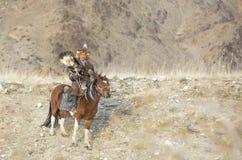在他的hotse的蒙古游牧人老鹰猎人 库存照片