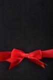 在黑皮革底部的红色丝带  免版税库存照片