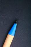 在黑皮革背景的蓝色笔书面材料 免版税库存图片