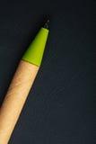 在黑皮革背景的绿色笔书面材料 库存照片