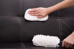 从在黑皮革长沙发使用的蒸气清洁法机器的白色织品刷子,手有布料的摩擦沙发 免版税库存图片